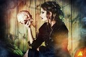 Attractive witch girl in medieval dress holding a skull in a mysterious abandoned house. Witchcraft, witch. Vampire.  Halloween concept. poster