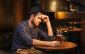 people, loneliness, alcohol and lifestyle concept - unhappy single young man in hat drinking beer at bar or pub poster