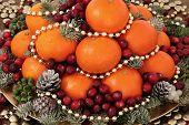 Christmas satsuma orange and cranberry fruit, gold bead decorations, holly, mistletoe and winter greenery over oak background. poster