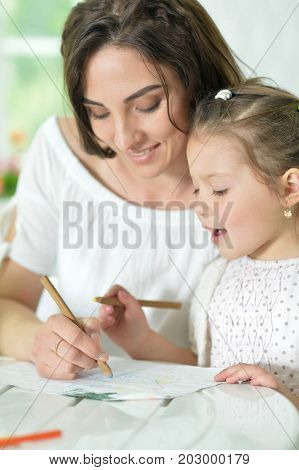 Happy mother and her cute little daughter drawing with pencils together