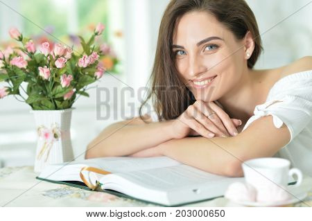 Beautiful young woman sitting at table and reading interesting book