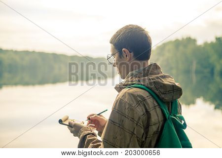 Photo of man in glasses with notebook on river bank in afternoon