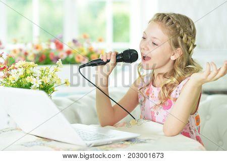 Adorable little girl using modern laptop and singing karaoke