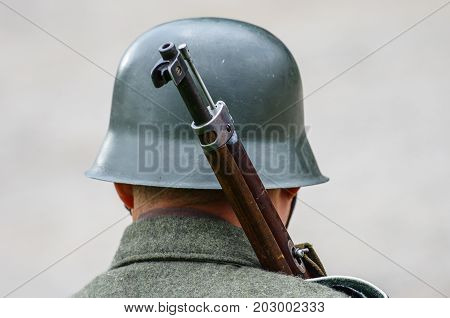 Soldier with old helmet and vintage weapon