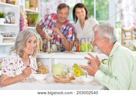 senior couple eating at kitchen table while spouse cooking on background