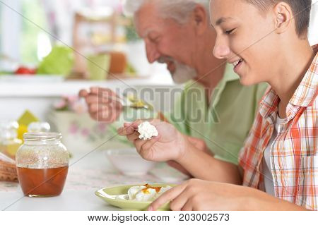 Grandfather and grandson sitting at table and having breakfast