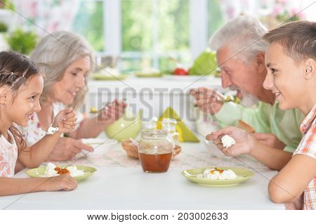 Happy Senior couple having meal with grandchildren at home