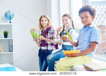 Adorable school learners with containers eating sandwiches on windowsill