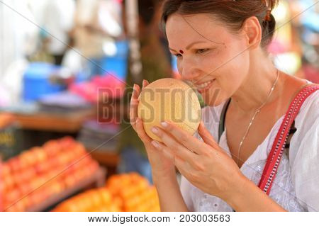 Portrait of a young woman sniffing fruit before buying