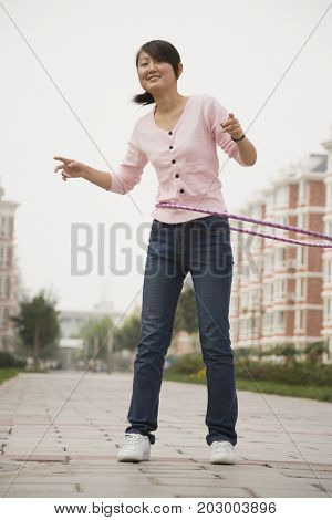 Chinese woman playing with plastic hoop