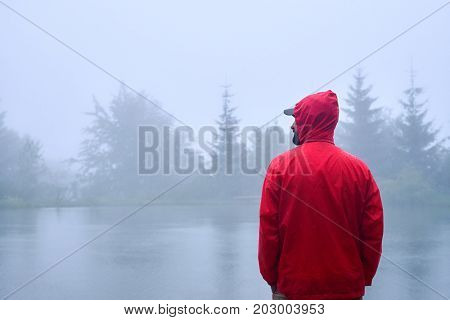 Back view of traveler in red waterproof jacket looking on the left near lake