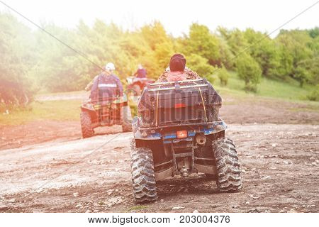 Tourists on a few quad bikes ride on rough terrain on a sunny day in the spring. Toned photo
