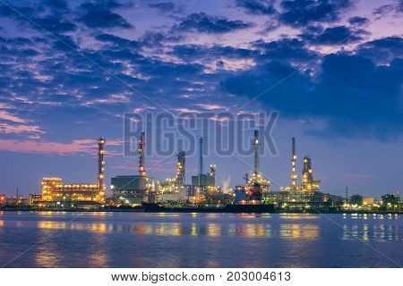 Oil refinery plant and shipping loading dock at twilight scene. Oil and Gas industry.