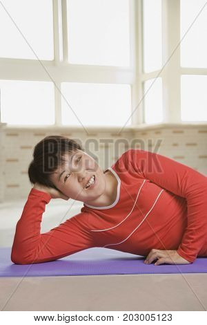 Chinese woman laying on exercise mat