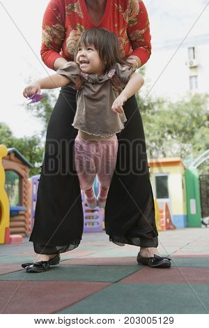Chinese grandmother lifting granddaughter