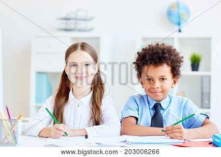 Two adorable learners sitting by desk in classroom
