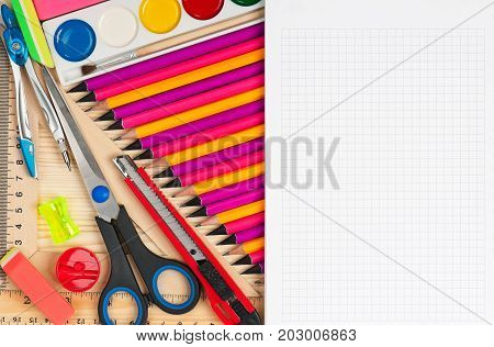 Bright writing materials for learning on a wooden surface with blank billboard for your text