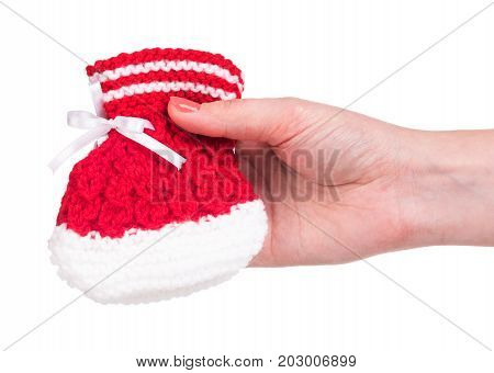 Cute little bootee in the female hand isolated over white background
