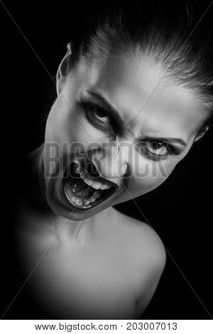 angry nude girl screaming at camera on black background, monochrome