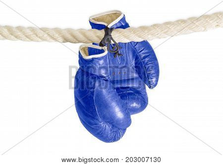 Old worn leather blue boxing gloves that hang on a laces on the rope of a boxing ring on a white background