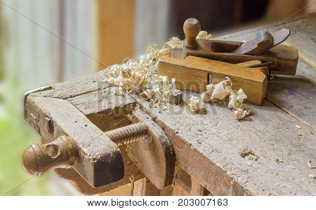 Fragment of old woodworking workbench with planing stop and shoulder vise with wooden screw two wooden hand planes lying on workbench among a shavings