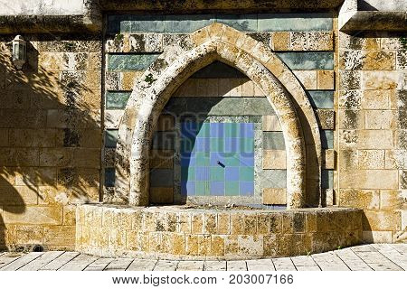 Aged Drinking Fountain in old Acre in Israel. Arab architecture of the old city of Akko.