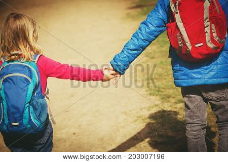 little boy and girl with backpacks going to school or daycare