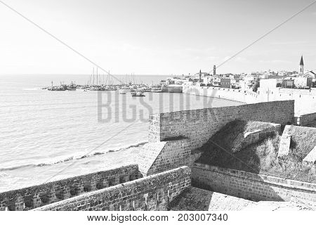 Embankment and city beach of old arabic city Akko located north of Israel. Sailboats moored at the marina in Acre. Black and white picture
