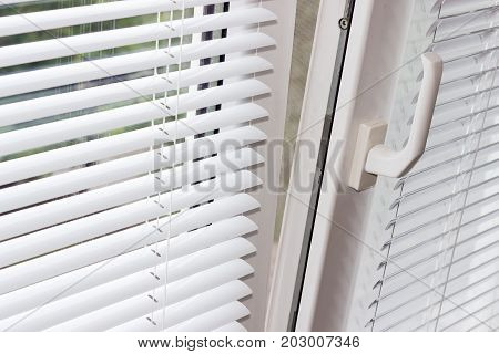 Fragment of the modern tilt and turn plastic window tilted inwards at the top with control handle and white Venetian blinds