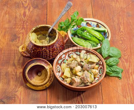 Ukrainian version of the dish Chanakhi in a clay bowl - potatoes with meat mushrooms and haricot beans roasted in a clay pot and lightly salted cucumbers on a surface of an old wooden planks