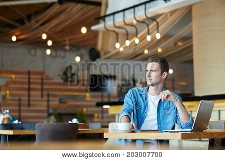 Young designer or specialist contemplating while sitting in cafe by cup of coffee