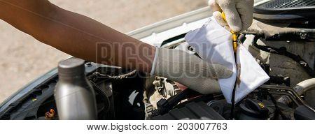 The man wipes the oil dipstick a white rag
