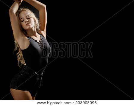 beautiful young woman show her slim body on black background with copy space