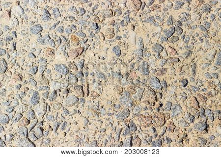 Texture of a fragment of the dirt track with inclusion of pink and gray granite gravel closeup