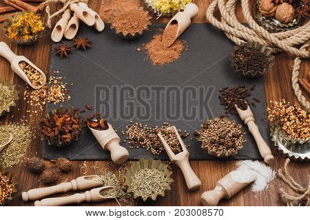 Different spices in bakeware with wooden scoops on the slate stone background soft focus background