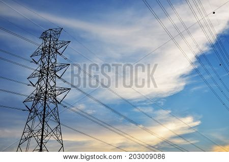Silhouette of electricity post on blue sky background.