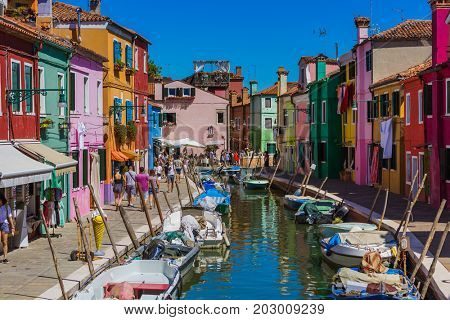 VENICE, ITALY - AUGUST 22, 2016: Tourists are walking at Burano village on August 22, 2016 in Venice Italy.