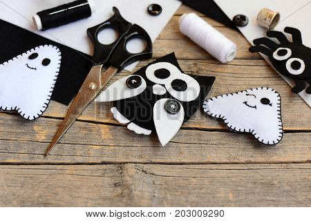 Halloween felt embellishments. Felt ghost, spider, owl embellishments on a vintage wooden table. Sewing tools and materials set. Quick and easy handmade crafts concept for kids. Closeup
