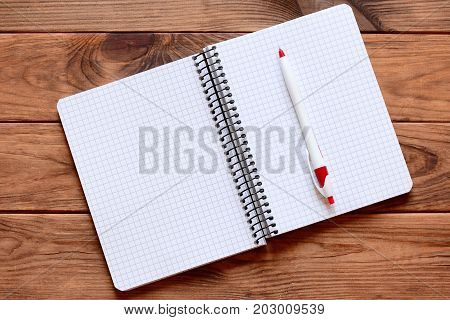 Blank open paper notebook for writing notes, pen isolated on wooden background. Paper notebook worksheet with empty copy space for text. Closeup. Top view