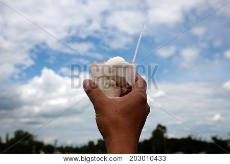 Hands of men hold an ice cream cup up to the sky to feels refreshed and look delicious.