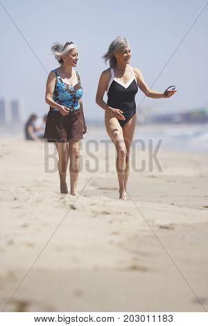 Friends in bathing suits walking on beach