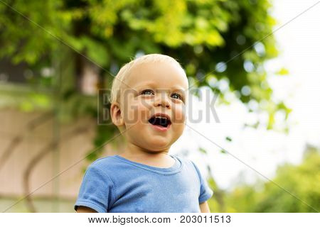 Close-up Portrait Of Cute Smiling Baby Boy On The Blurred Nature Background.