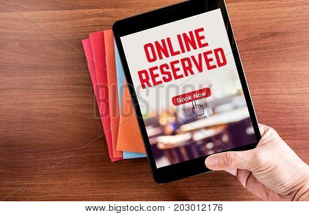 Top View Of Hand Holding Tablet With Online Reserved Word With Blur Restaurant Over Color Notebook O
