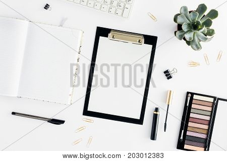 Home office workspace. Feminine workplace with clipboard eyeshadow mascara keyboard and notepad. Office table desk. Top view. Flat lay