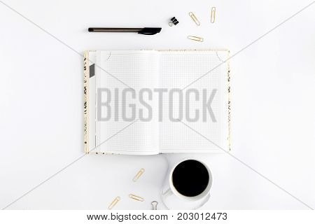 Open feminine notepad with cup of coffee on white background. Top view. Flat lay. Concept of feminine workplace