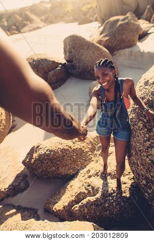Young woman walking through the rocks with support from her boyfriend. POV shot of man helping girlfriend climbing rock at the beach.