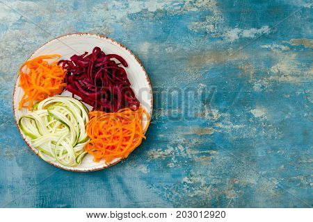 Zucchini carrot sweet potato and beetroot noodles on a plate. Top view overhead copy space. Blue rustic background