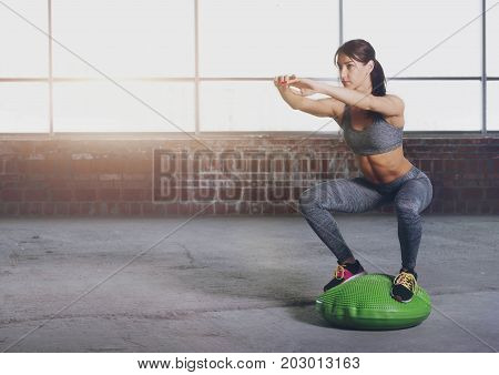 Young woman athlete in sportswear squat on gymnastic ball in front of window in loft interior