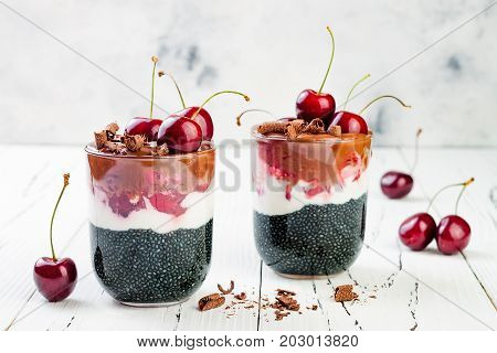 Healthy Black Forest dessert. Black activated charcoal chia pudding with cherries coconut cream and chocolate. Vegan creamy breakfast.