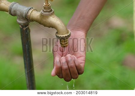 Water for African women - beautiful model holds hand under a water tap